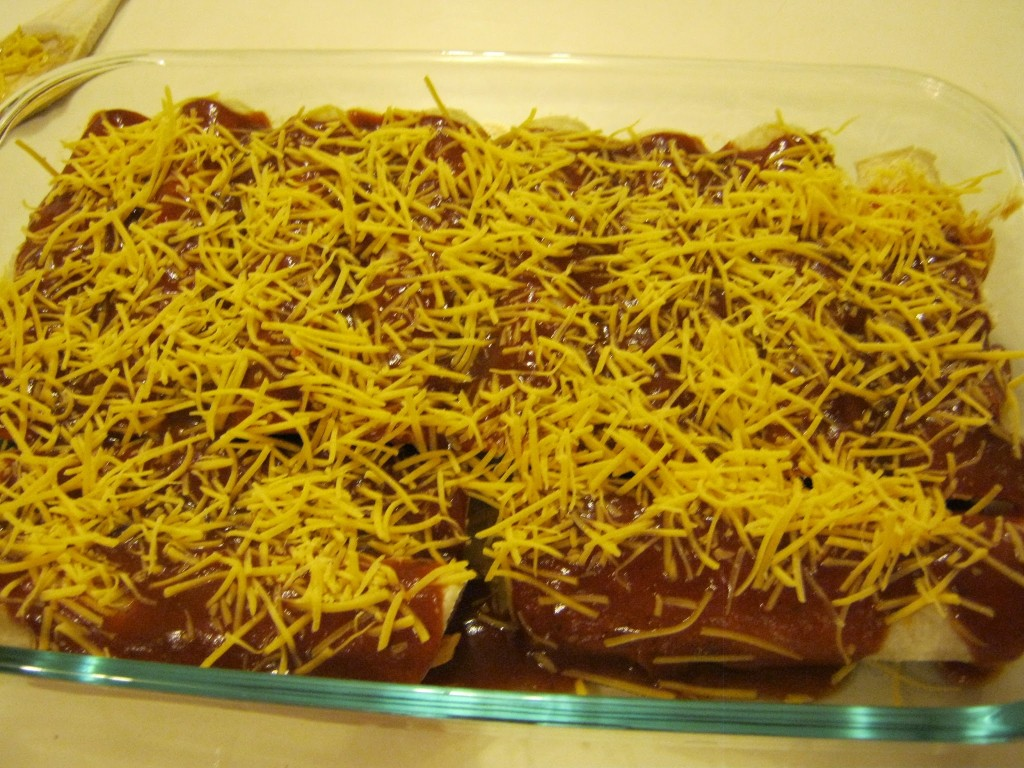 Enchiladas sprinkled with cheese and ready to cook