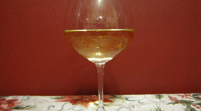 Dr. Heidemann's Riesling white wine with red wall behind.