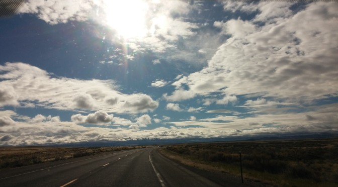 Open road with scattered clouds and the sun shining down.