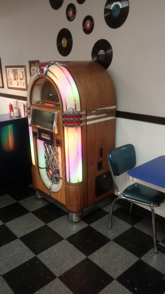 Jukebox, records on the wall, checkered floor, and a blue chair.