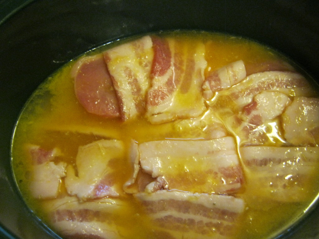 Bacon wrapped pork chops in orange juice in a Crock Pot